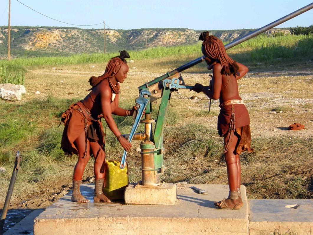 Två himbakvinnor i Namibia reparerar en handpump med stora rörtänger